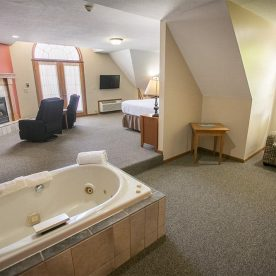 Jetted tub, fireplace, and seating area in Room 6