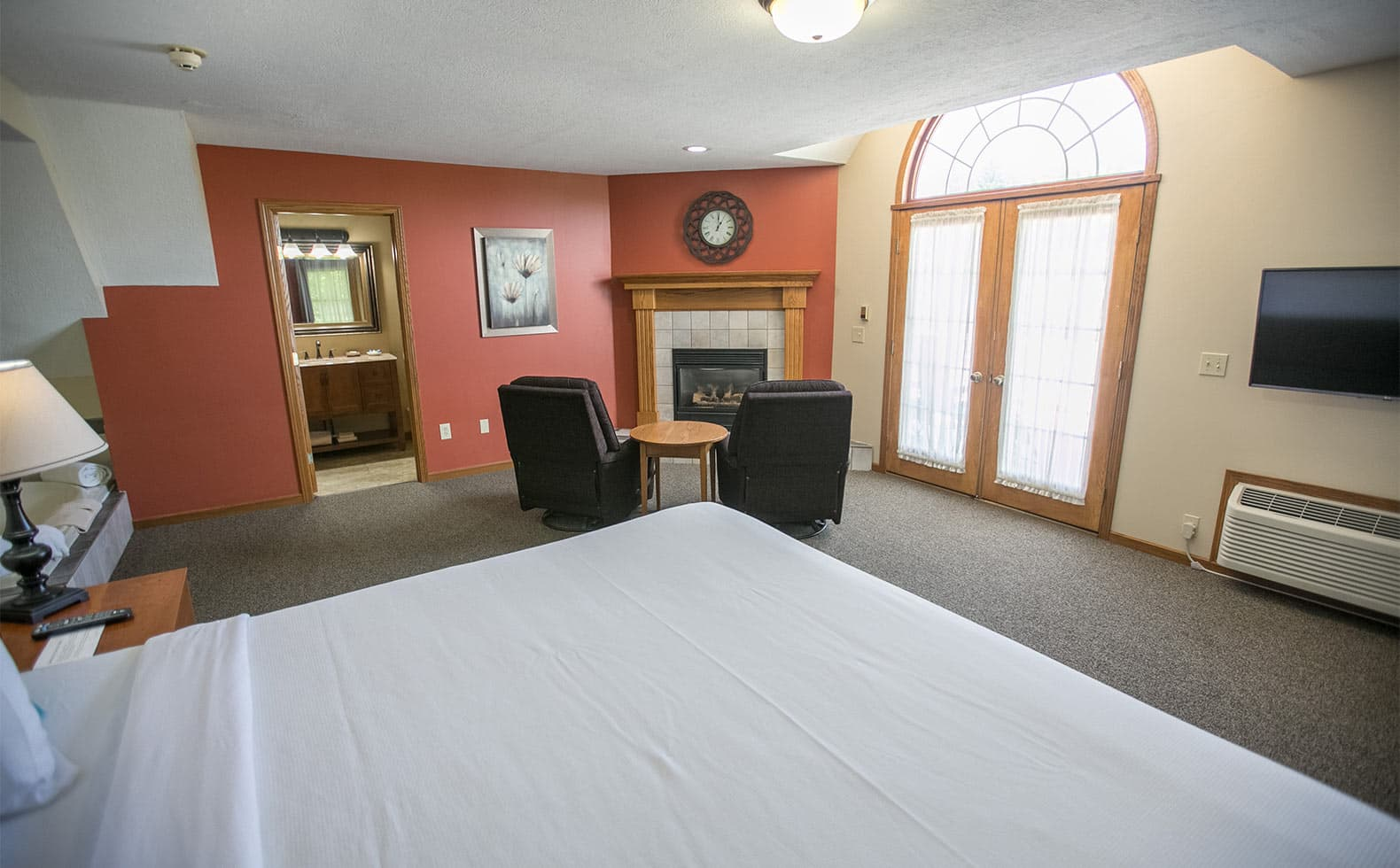 Fireplace with two comfy chairs, exterior door and King Bed