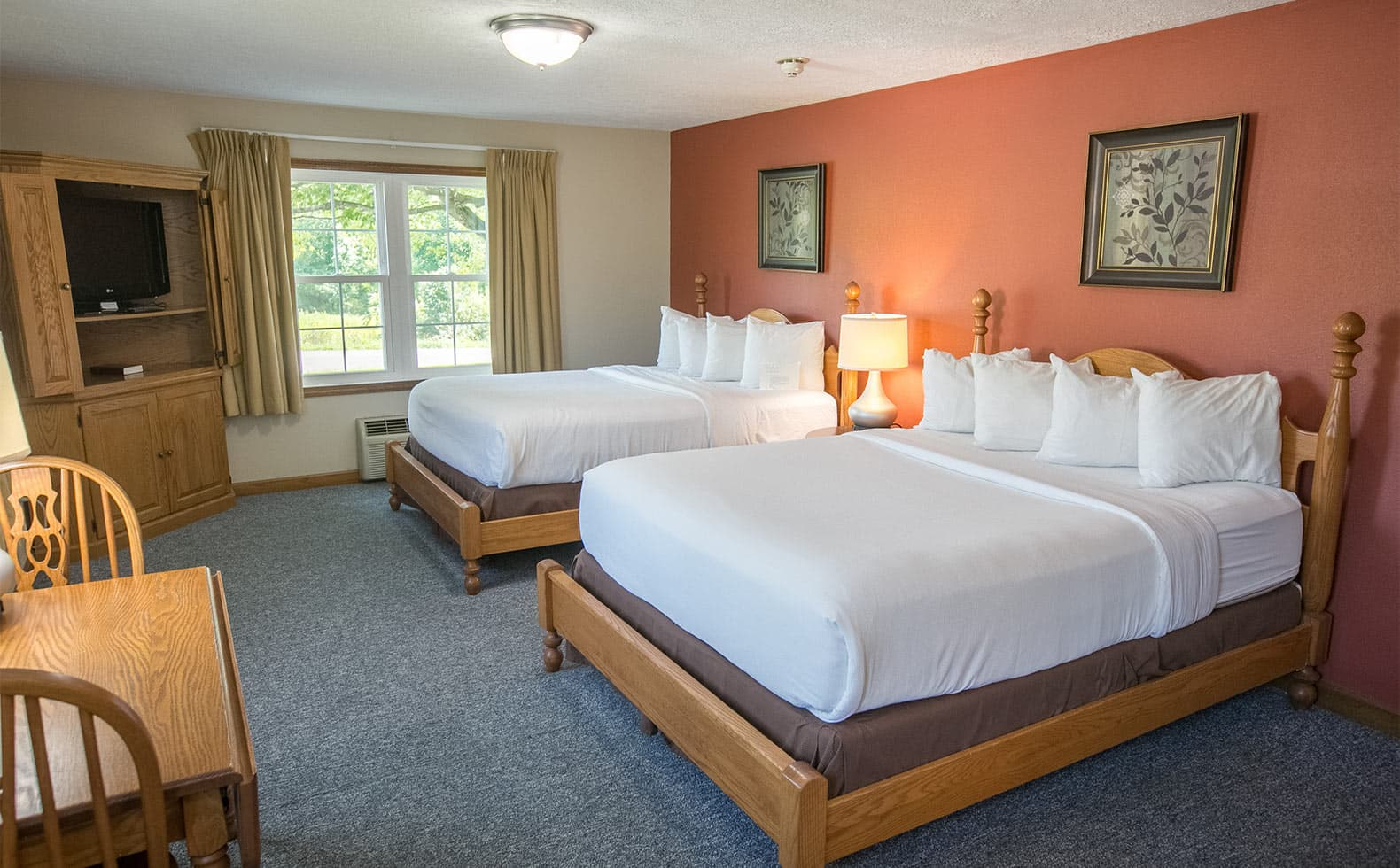 Two Queen Beds in Room 8 with Dining table and chairs.