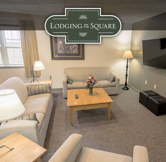 Lodging on the Square logo and suite living room